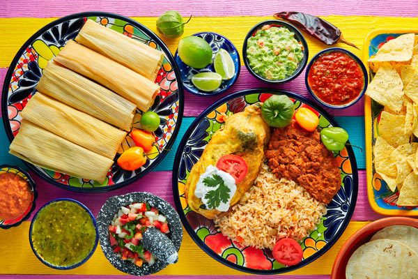 La Chalupa Lancaster Mexican food on colorful plate and table including tamales, rice and beans, dips and sauces